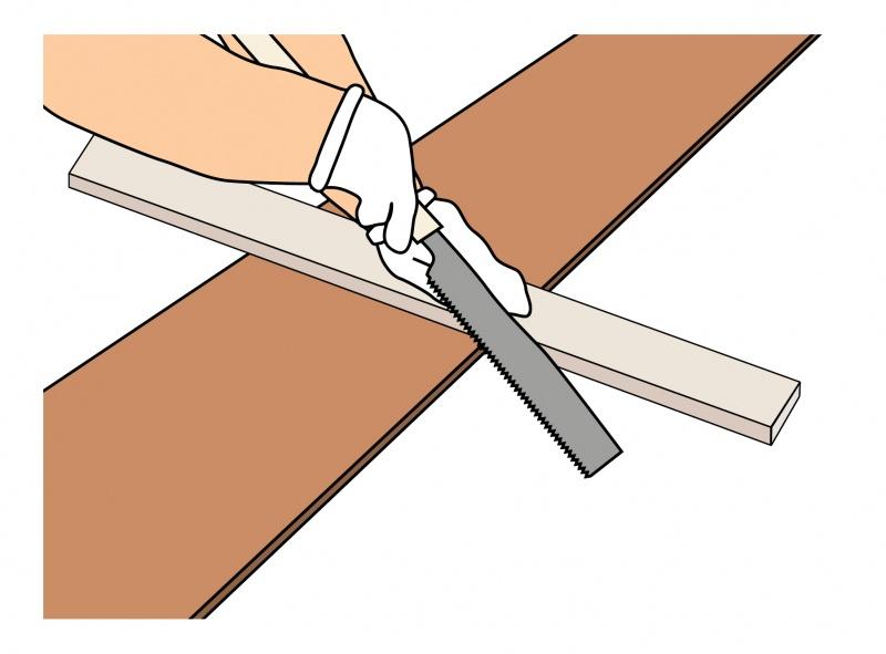 角材を定規代わりにしてノコギリで切る